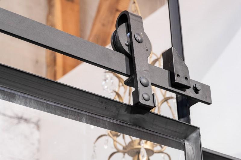 Detail stalen loftdeur met wielen in het zicht